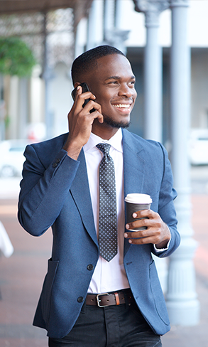 Business man smiling and walking outside while talking on cellphone